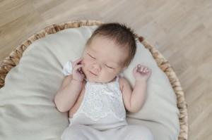 Babyfotograf Hamburg - Baby liegt lächelnd im Körbchen