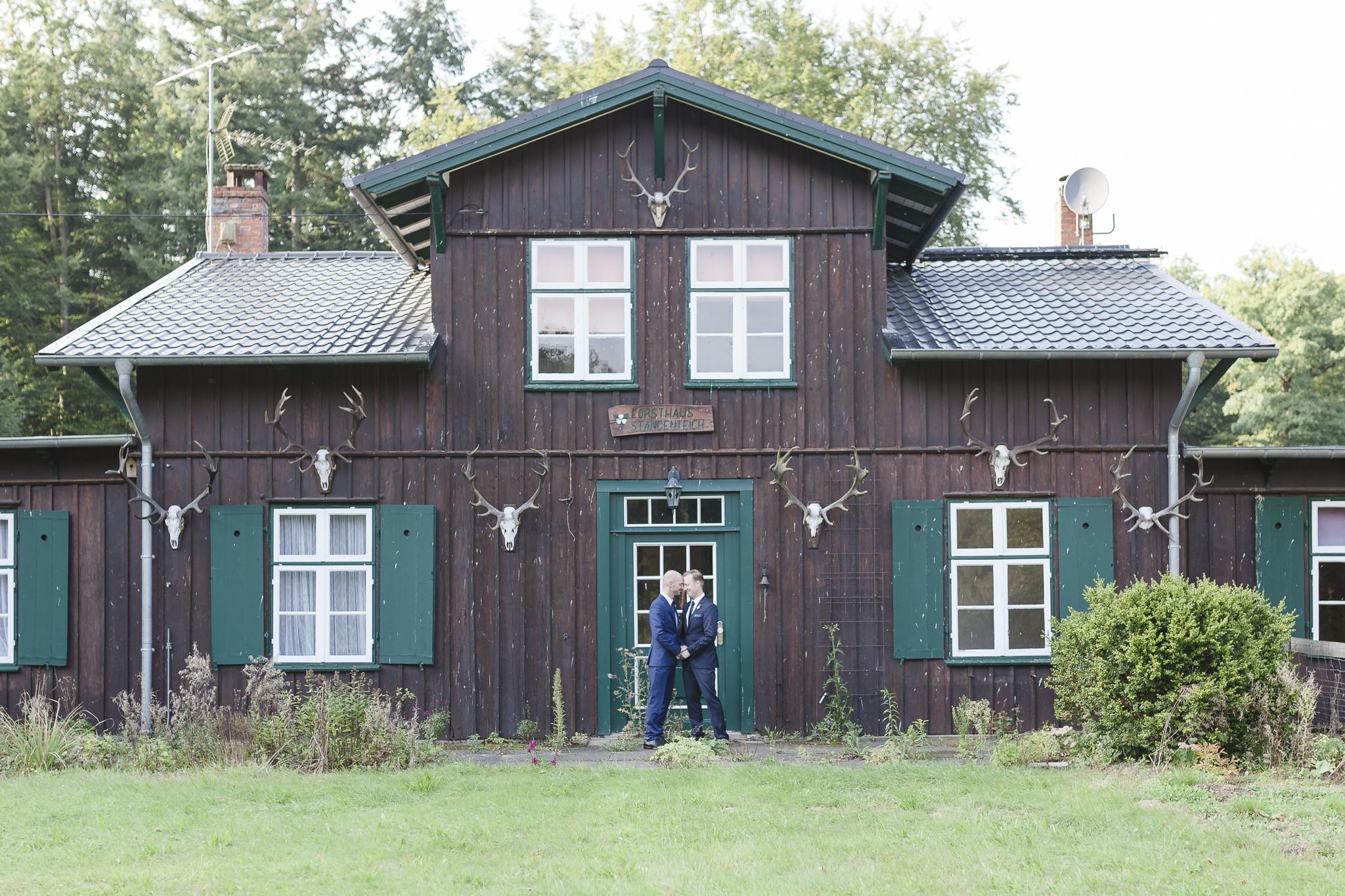 Hochzeitsfotograf Hamburg - schwules Brautpaar steht vor Jagdhütte