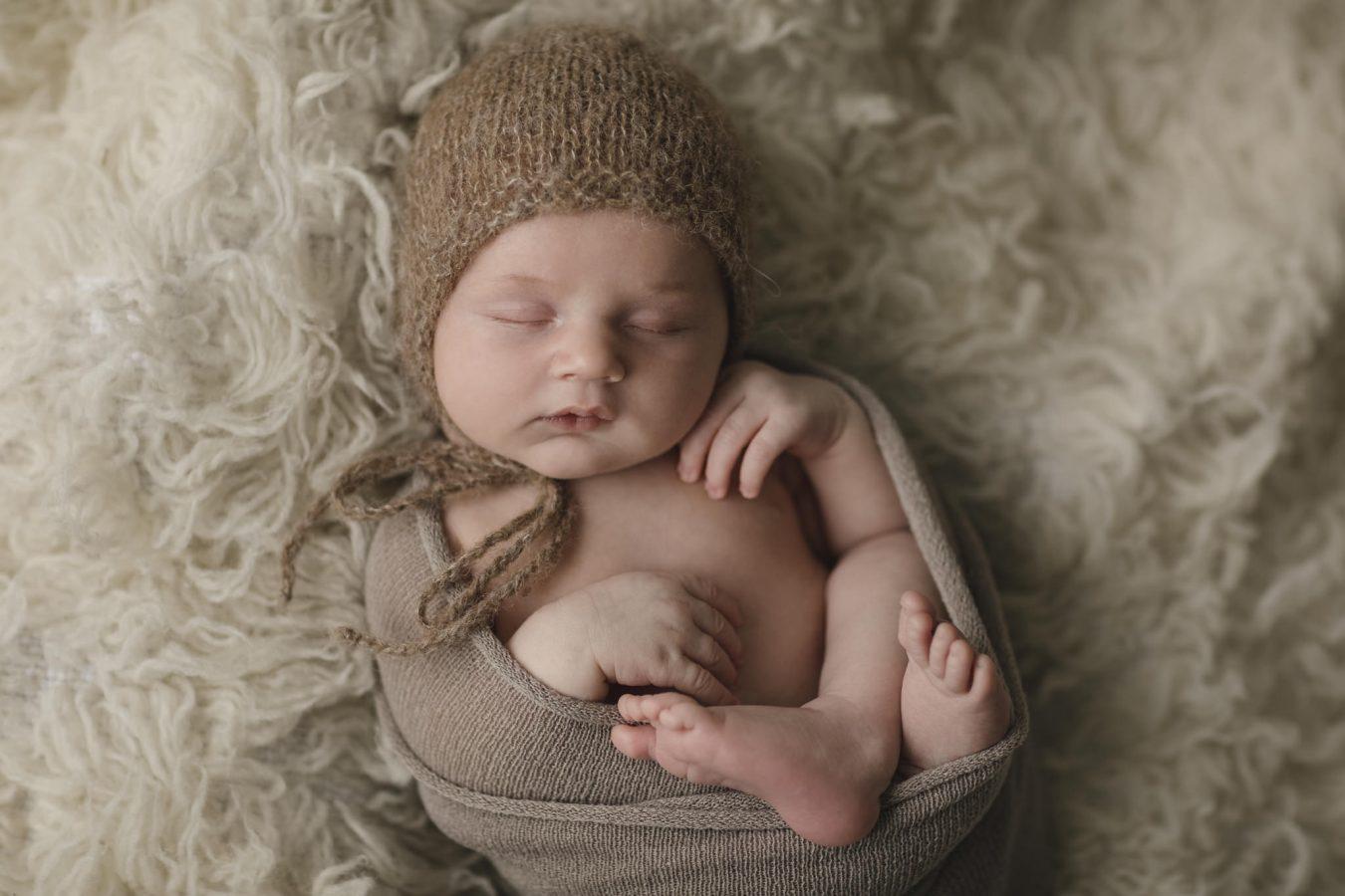 Babyfotograf Hamburg - Baby liegt in einen Wrap gewickelt auf einem kuscheligen Fell
