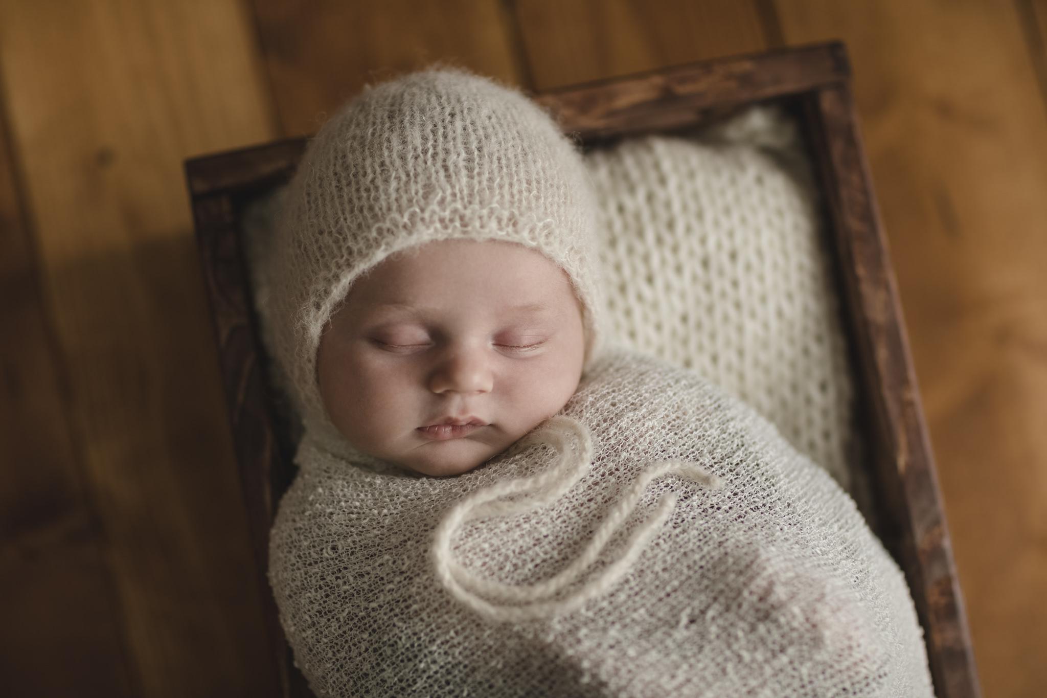 Babyfotograf Hamburg - Baby liegt beim Newbornfotoworkshop eingewickelt in einem Körbchen