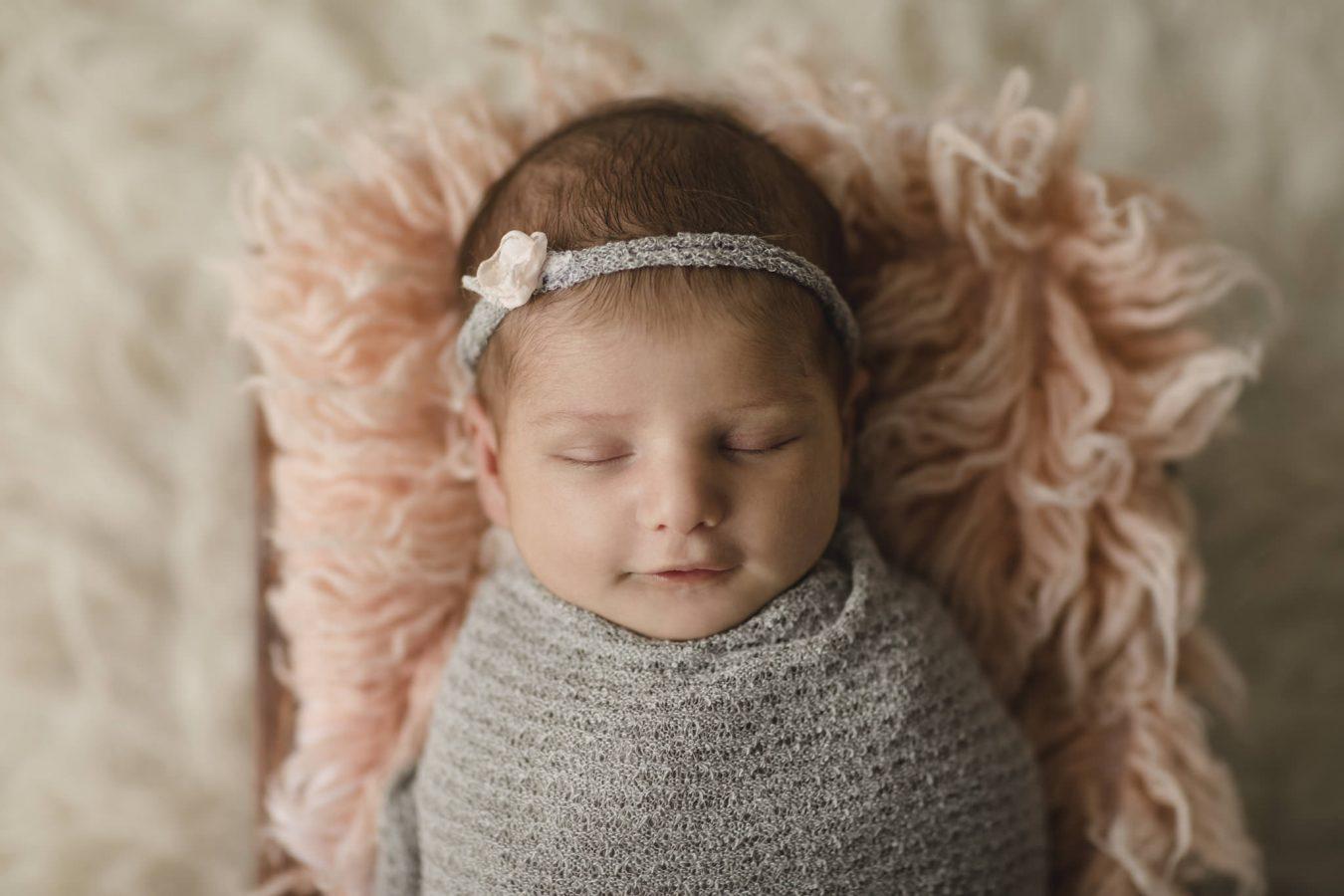 Babyfotograf Hamburg - Baby liegt eingewickelt in einer Kiste