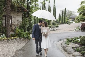 Hochzeitsfotograf Hamburg - Paar läuft unter Schirm den Weg entlang
