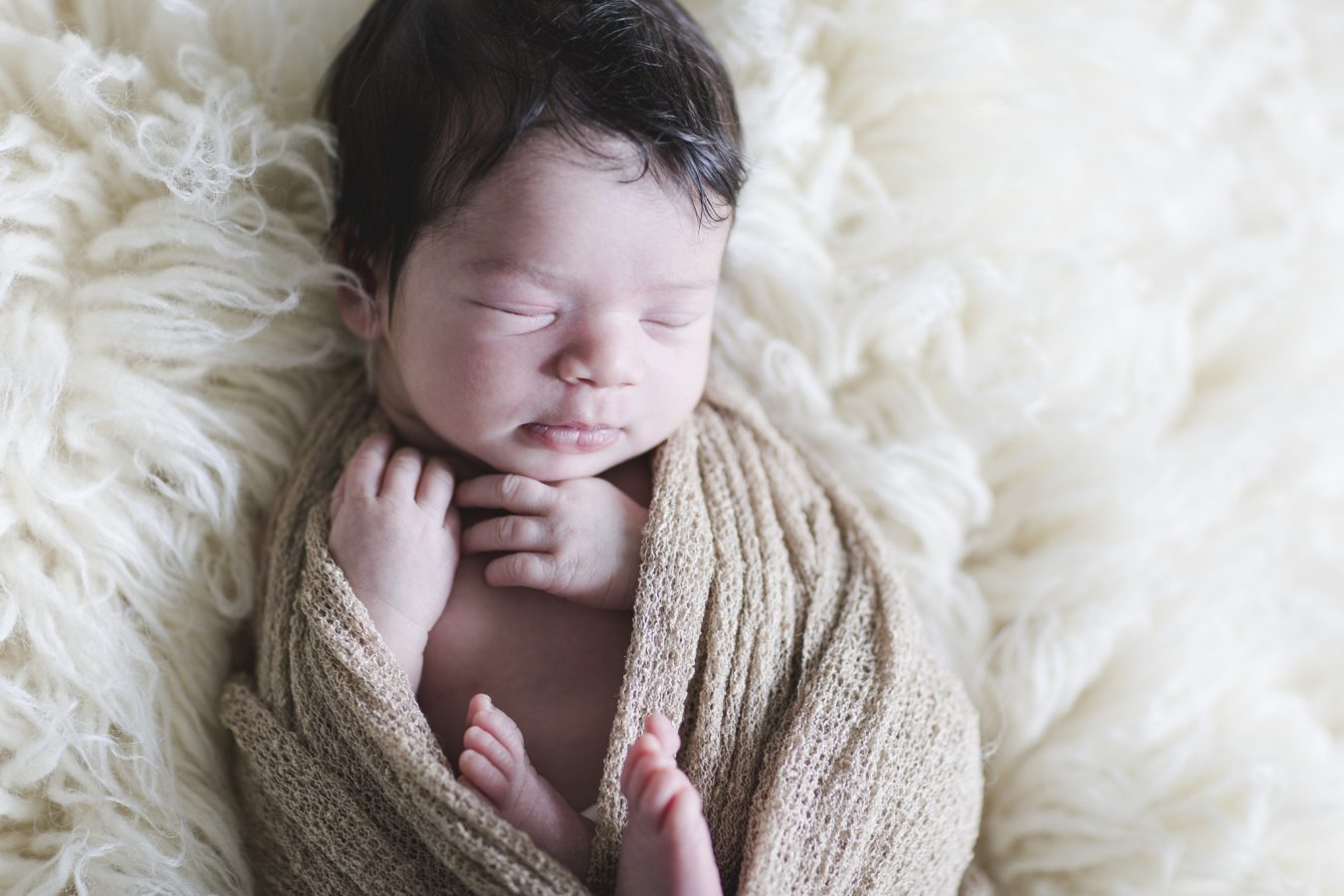 Babyfotograf Hamburg - Baby liegt in ein Tuch gewickelt auf einem Flokati
