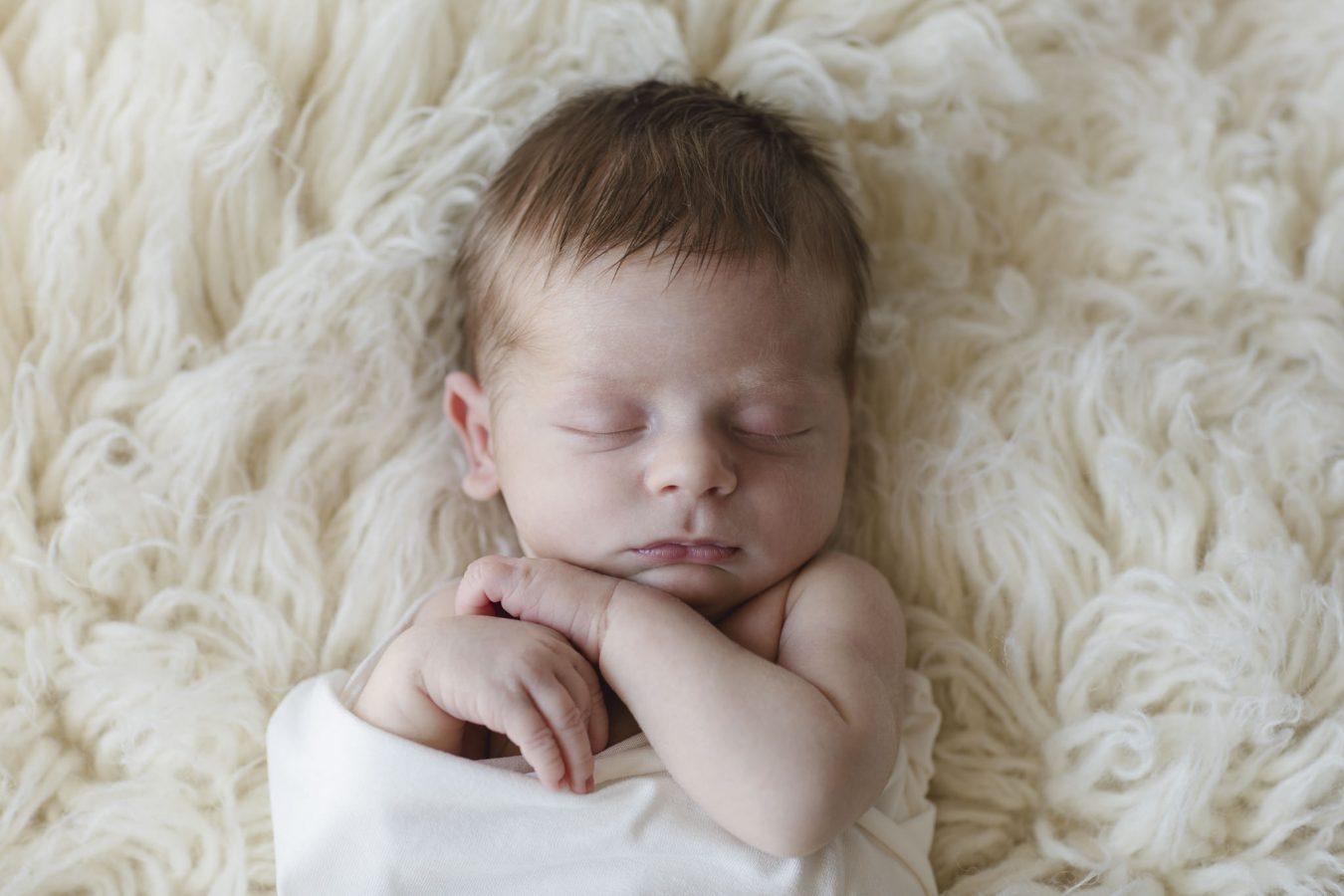 Babyfotograf Hamburg - Baby liegt in einem Wrap eingewickelt auf einem Flokati und schläft