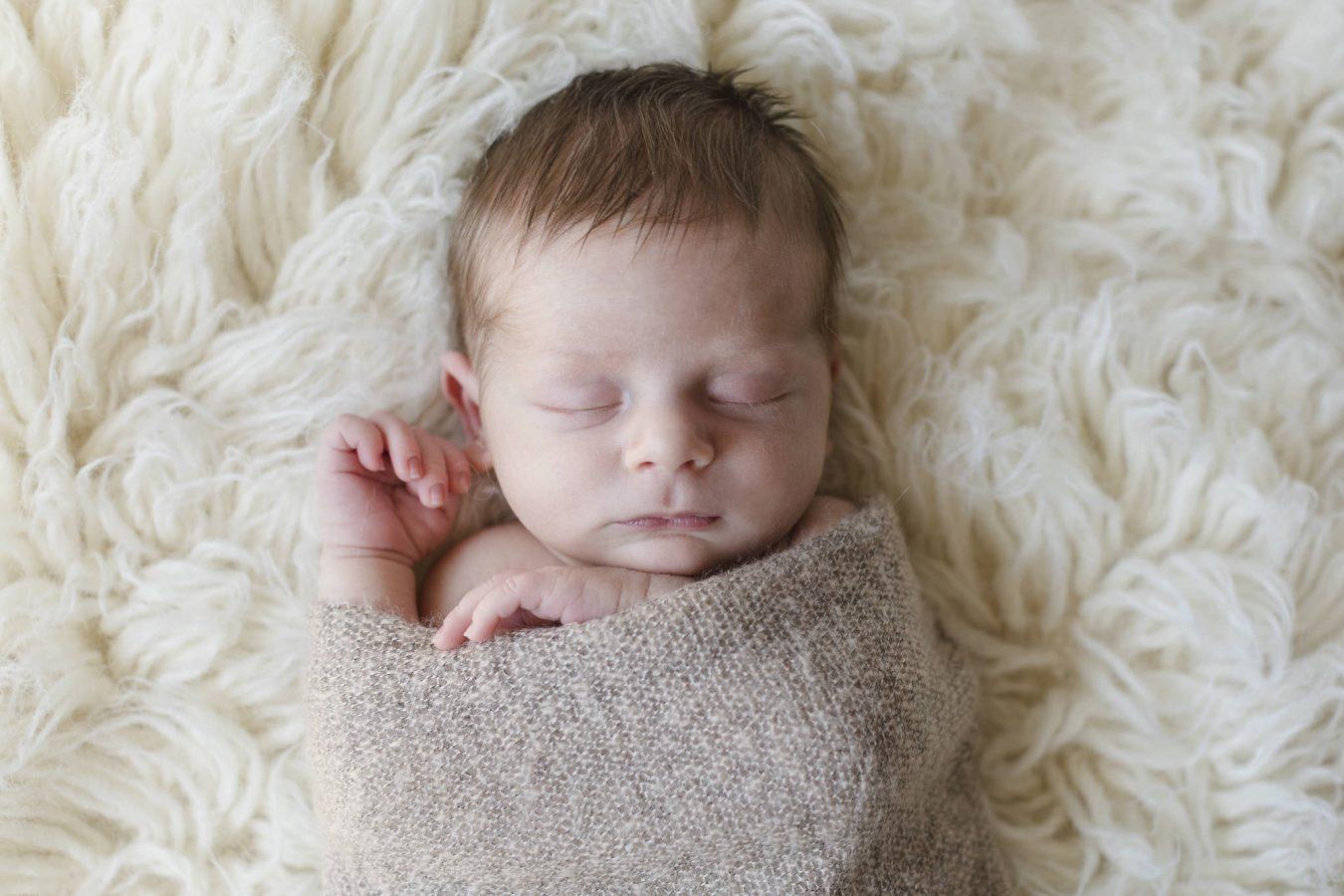 Babyfotograf Hamburg - Baby liegt in einen Wrap eingewickelt auf einem Flokati und schläft