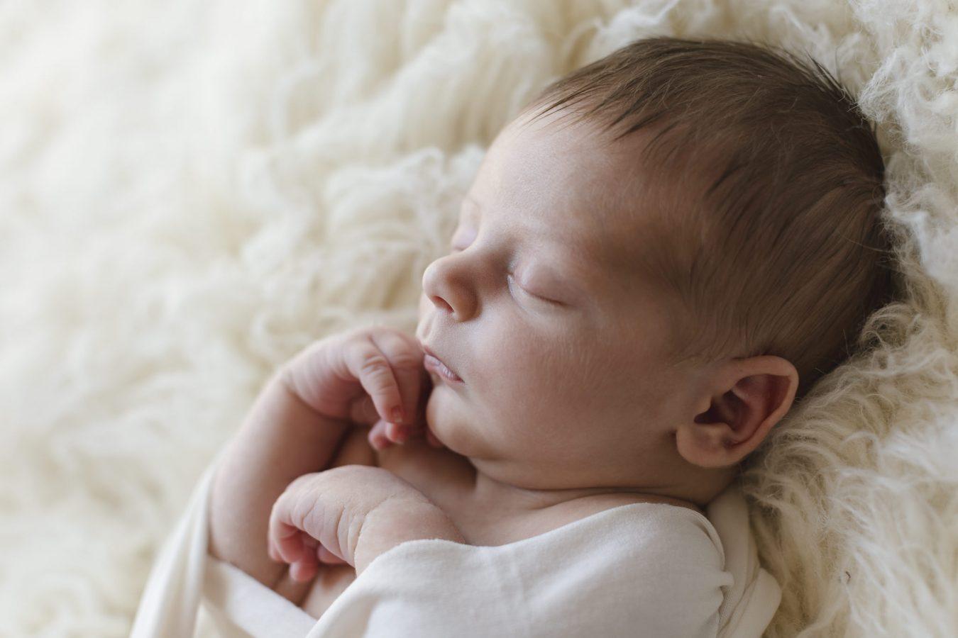 Babyfotograf Hamburg - Baby liegt auf Flokati und schläft
