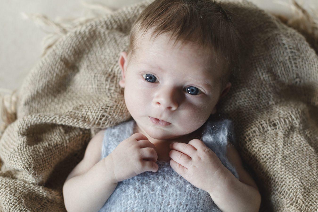 Babyfotograf Hamburg - Baby liegt auf Jutedecke und schaut ganz neugierig in die Kamera