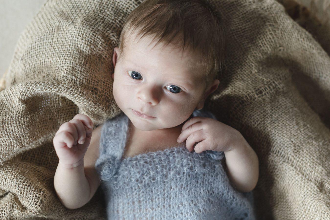 Babyfotograf Hamburg - Baby liegt auf Jutedecke und schaut neugierig in die Kamera