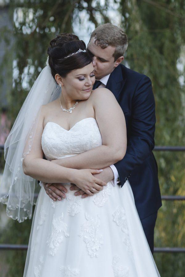 Hochzeitsfotograf Hamburg - Brautpaar steht eng umschlungen unter Trauerweide