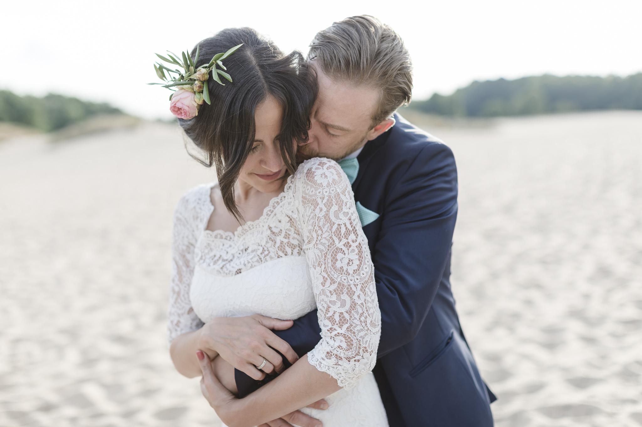 Hochzeitsfotograf Hamburg - Brautpaar steht in Sanddüne und kuschelt sich ganz eng aneinander