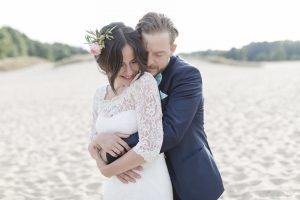 Hochzeitsfotograf Hamburg - Brautpaar kuschelt sich in Sanddüne eng aneinander