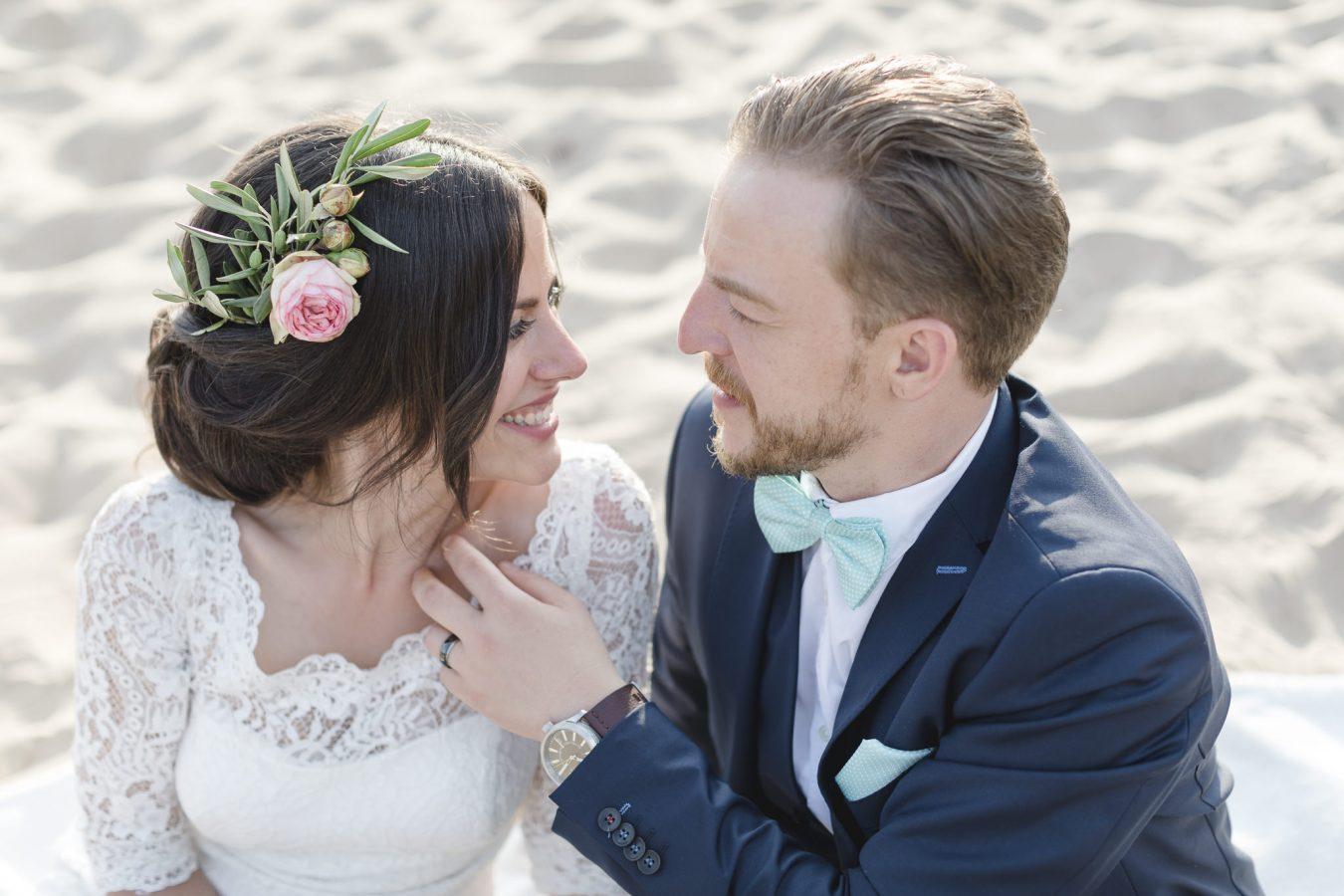 Hochzeitsfotograf Hamburg - Brautpaar sitzt im Sand und schaut sich ganz verliebt an