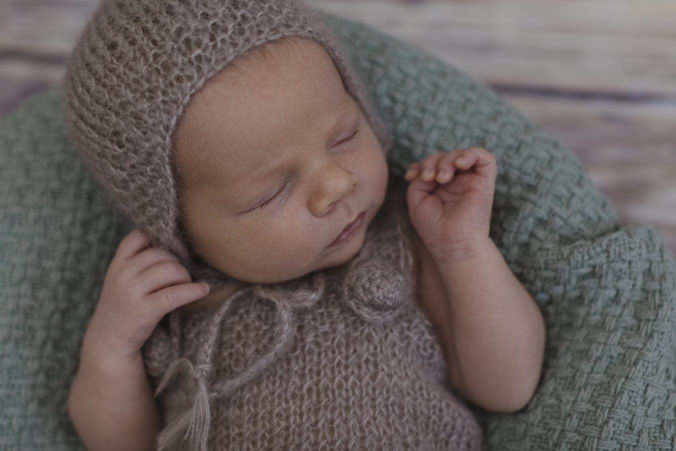 Babyfotograf Hamburg - Baby liegt in Körbchen und hat eine Mütze auf