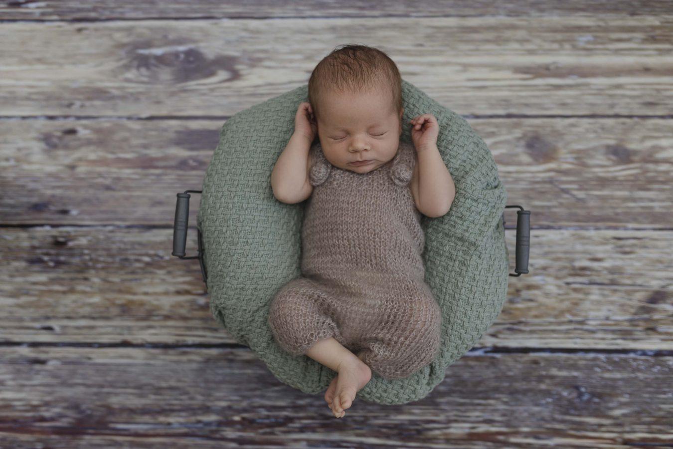 Babyfotograf Hamburg - Baby liegt auf grüner Decke in einem Körbchen