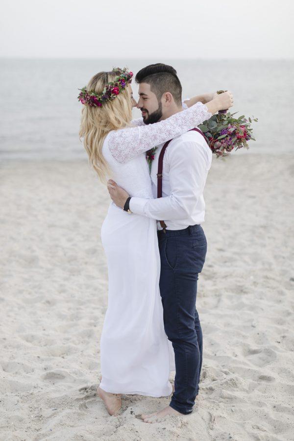 Strandhochzeit - Brautpaar steht eng umschlungen am Strand