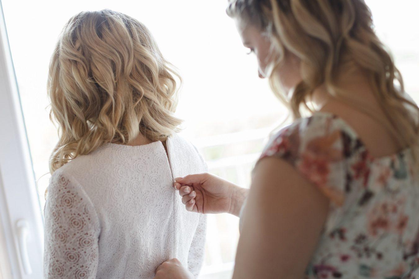 Hochzeitsfotograf Hamburg - Strandhochzeit - Trauzeugin schließt das Kleid der Braut