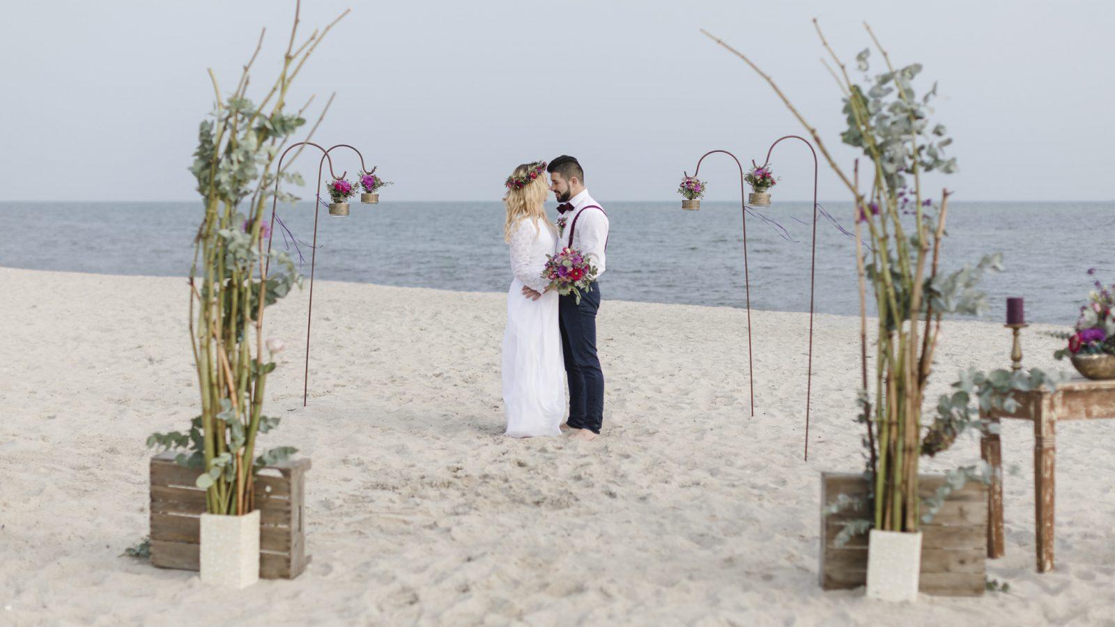 Strandhochzeit - Brautpaar steht im Blumenbogen und schaut sich verliebt an