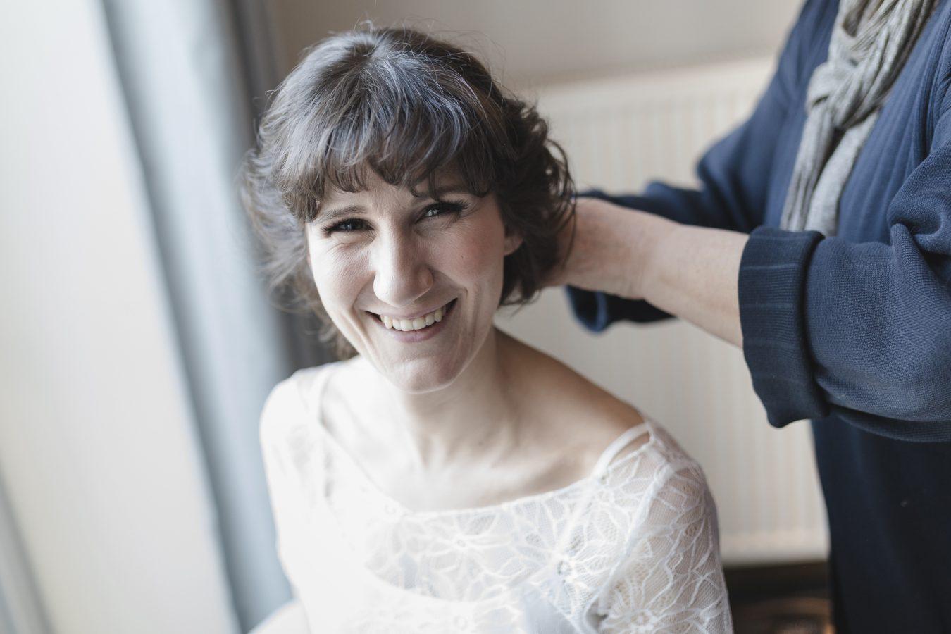Hochzeitsfotograf Hamburg - Braut lacht beim Styling in die Kamera