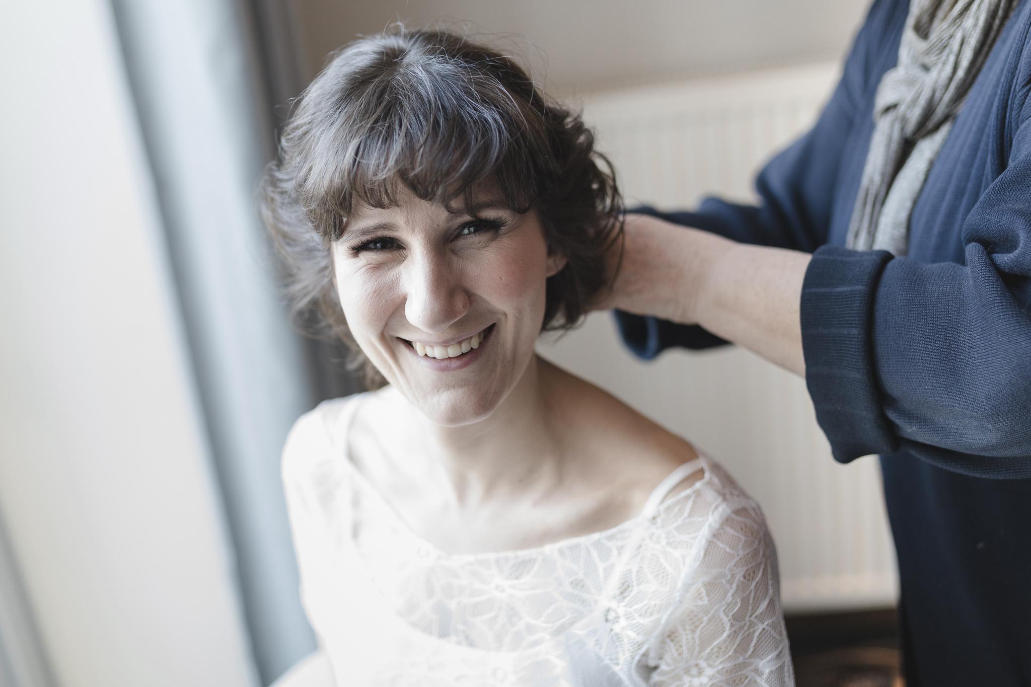 Hochzeit in Hamburg - Braut lacht beim Styling in die Kamera