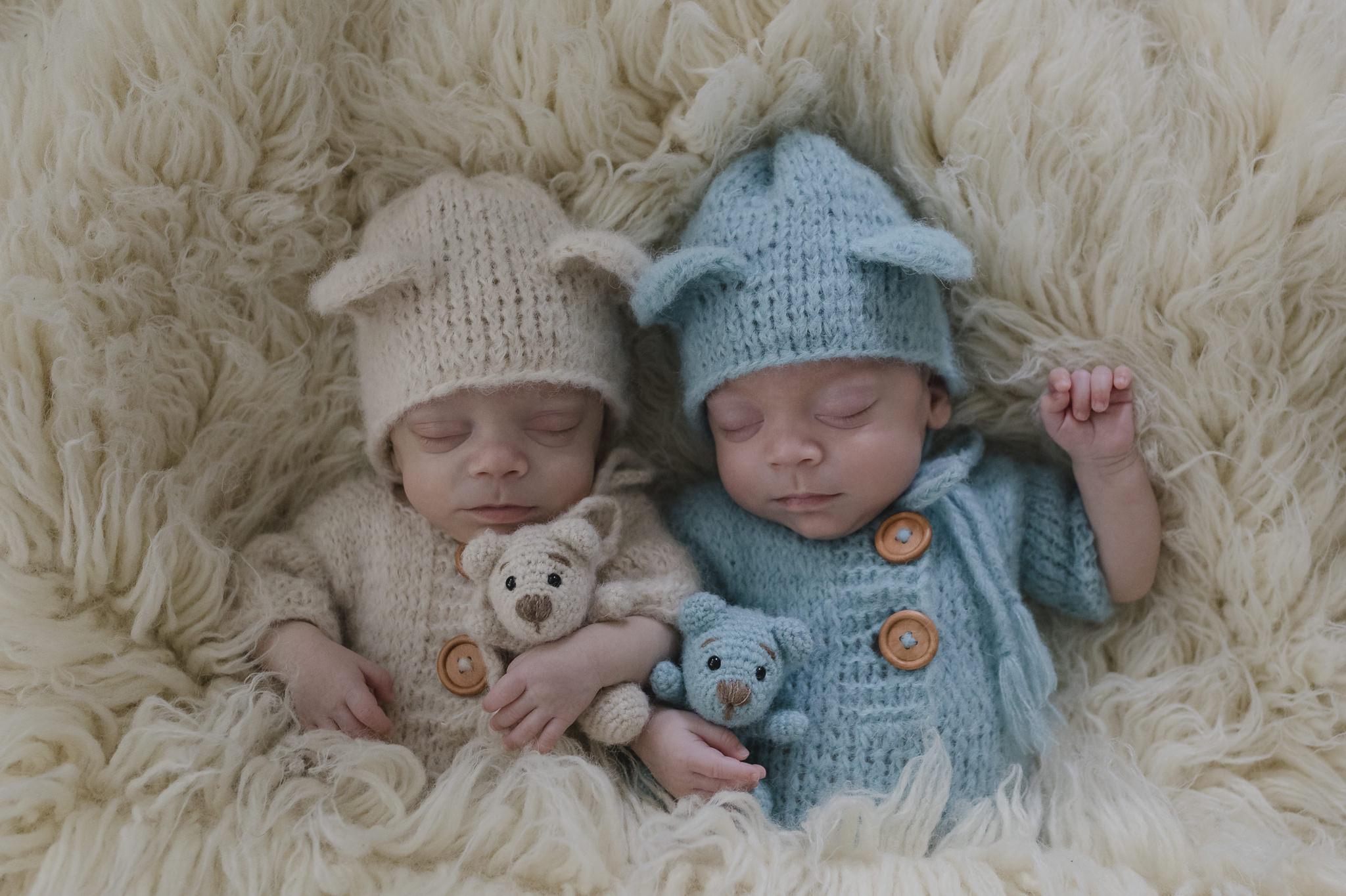 Babyfotograf Hamburg - Zwillinge liegend schlafend auf Flokati mit Bärchen im Arm