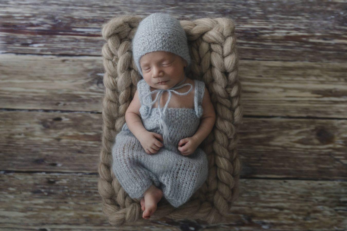Babyfotograf Hamburg - Baby liegt in blauem Strampler im Körbchen und schläft