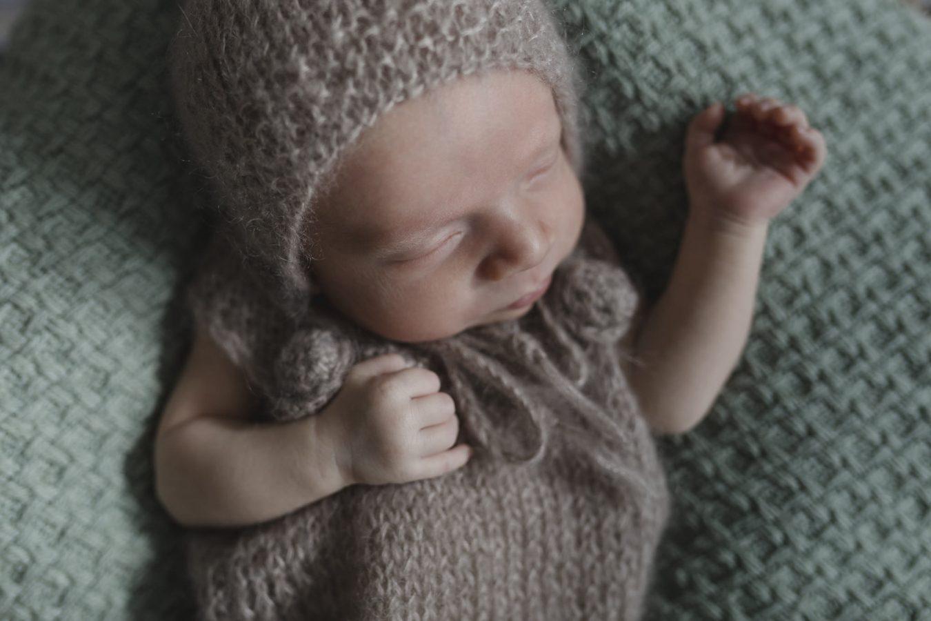 Babyfotograf Hamburg - Baby trägt braunen Strampler und schläft