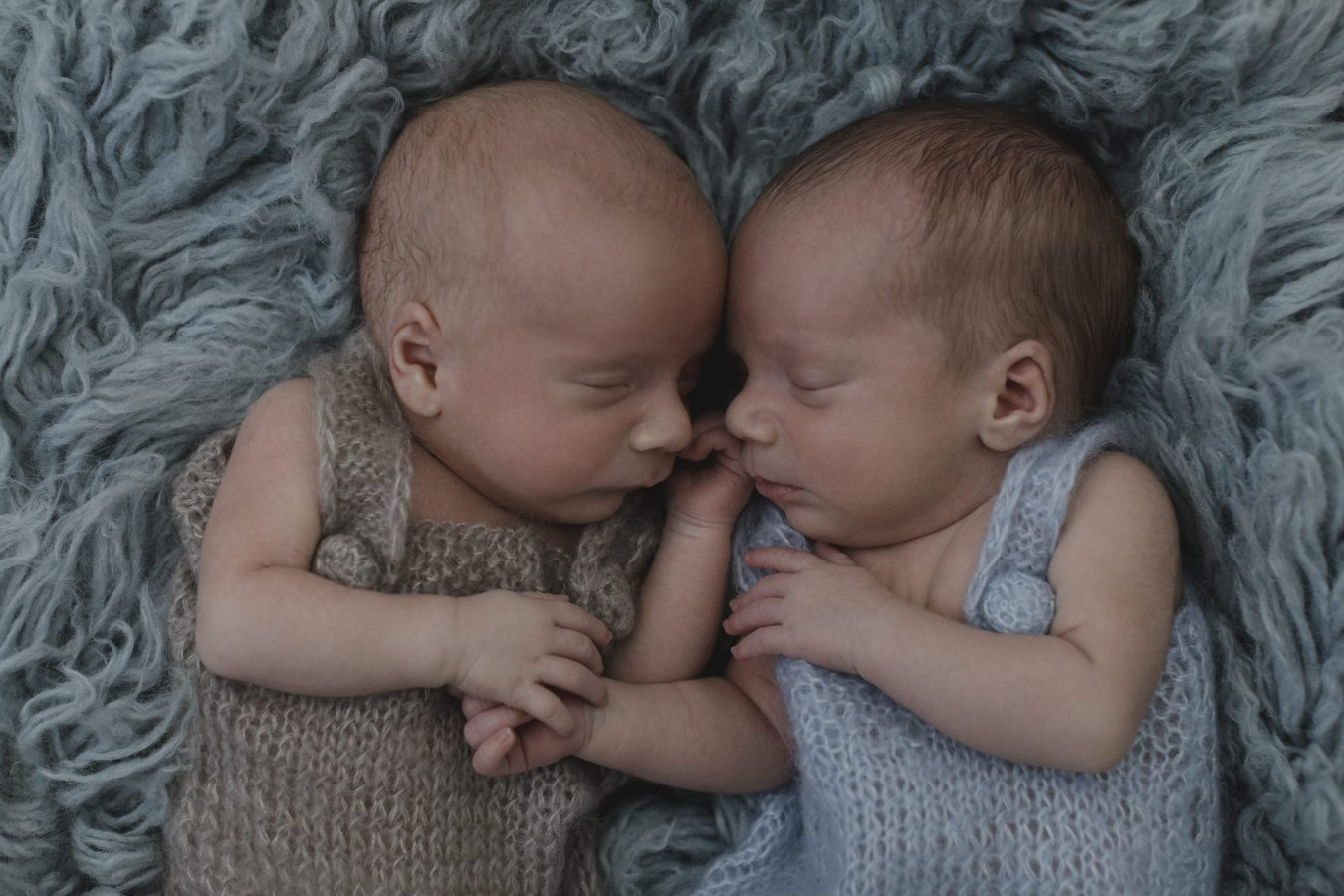 Babyfotograf Hamburg - Zwillinge liegen schlafend nebeneinander und halten sich an den Händen