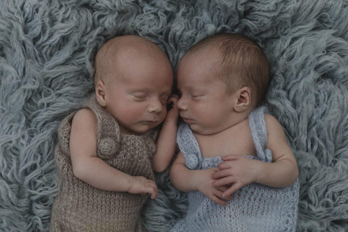 Babyfotograf Hamburg - Zwillinge liegen nebeneinander auf blauem Flokati