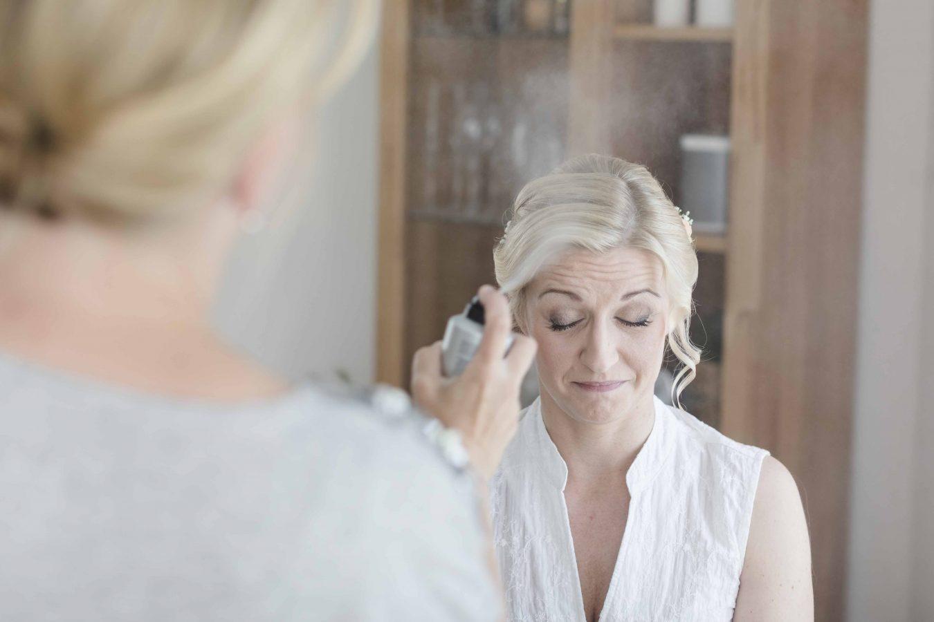 Getting Ready der Braut - die Frisur wird mit Haarspray fixiert