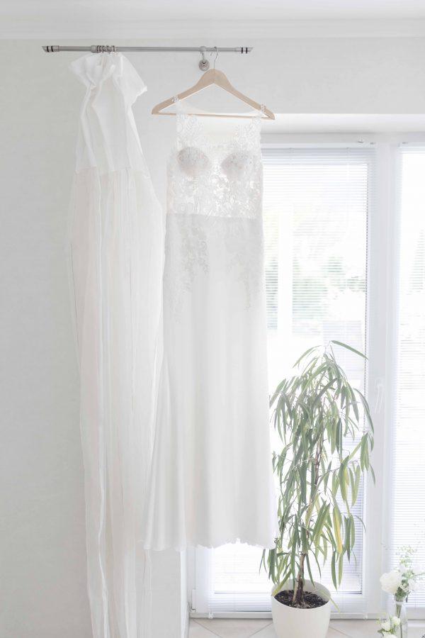 das Brautkleid hängt an der Gardinenstange