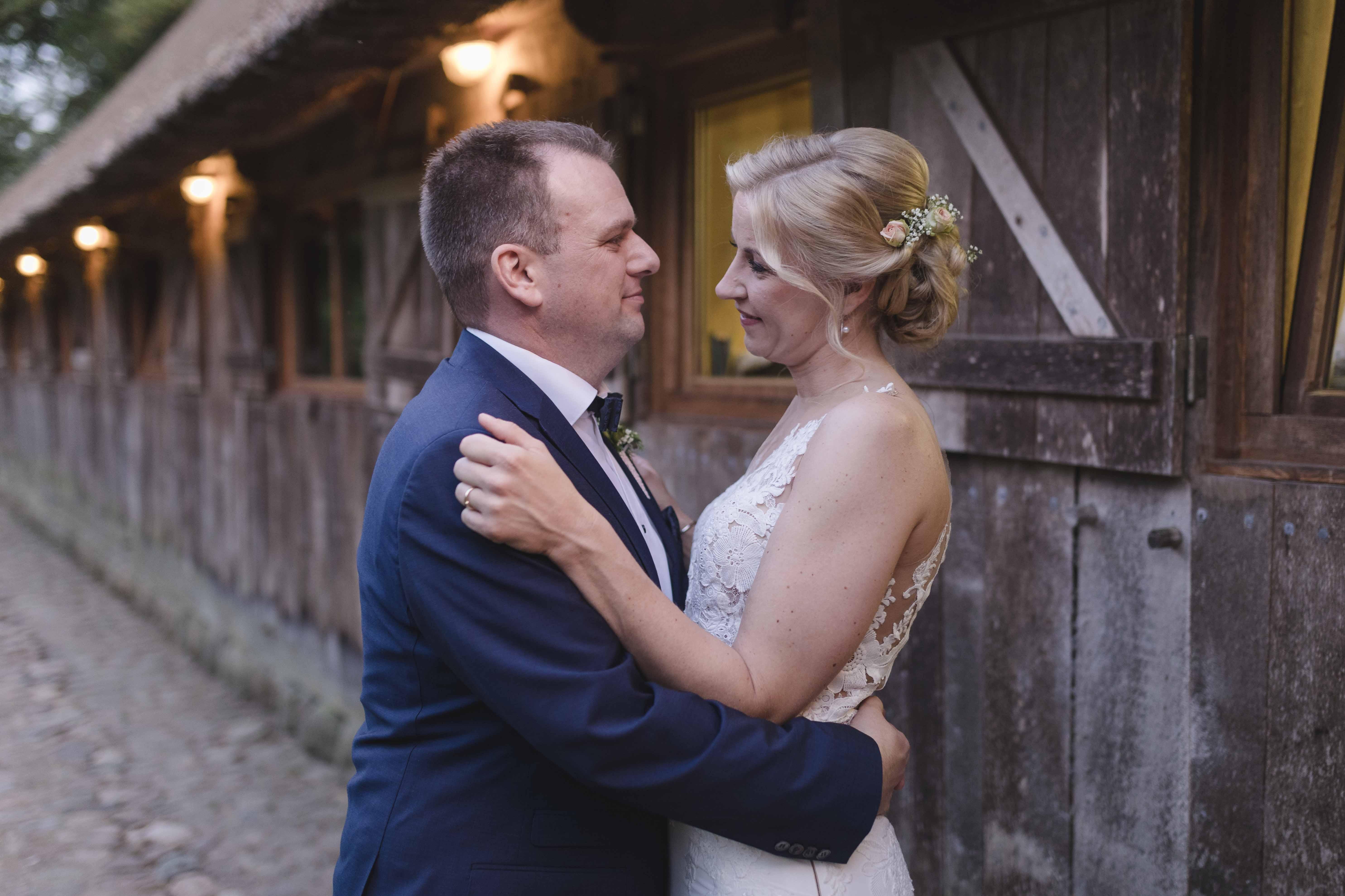 Paarshooting am Hochzeitstag - das Paar steht abends vor der beleuchteten Location