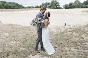 Brautpaar steht eng umschlungen in der Sanddüne