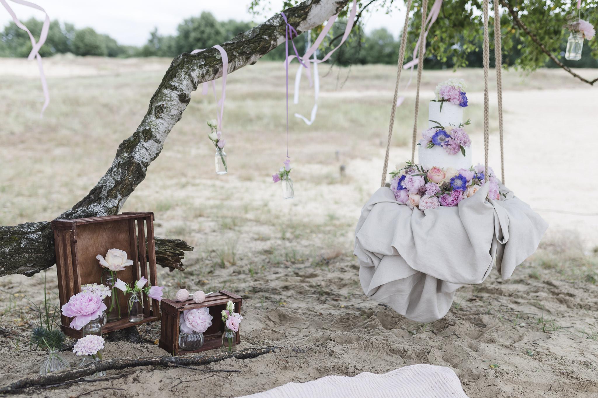 Hochzeitsinspirationen - die Hochzeitstorte hängt auf einer Schaukel im Baum