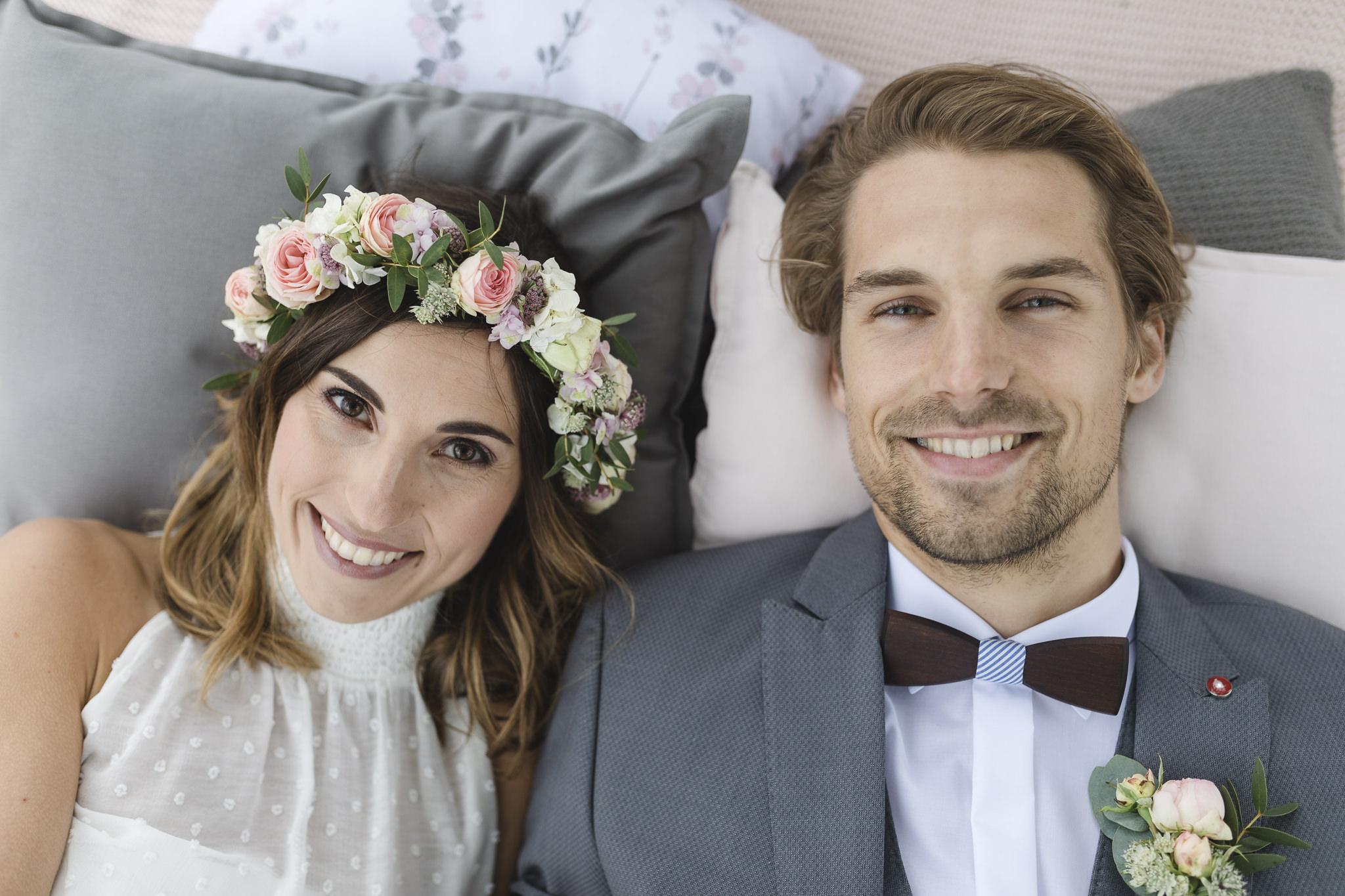 Hochzeitsinspirationen - Brautpaar liegt auf einer Decke und lacht in die Kamera
