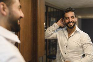 der Bräutigam bewundert das fertige Styling im Spiegel