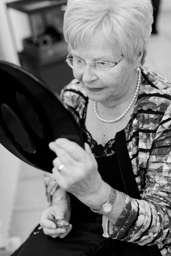Oma schaut beim Styling prüfend in den Spiegel