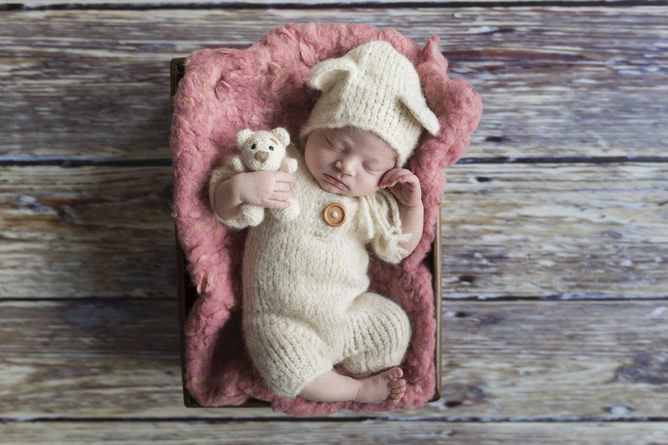 das kleine Mädchen liegt auf einer rosa Decke in einem Körbchen
