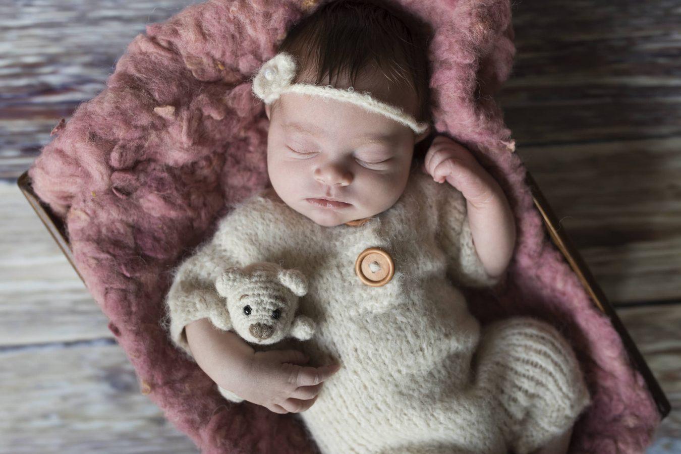 Babyfotografin Hamburg - das kleine Mädchen trägt ein Haarband passend zum Strampler