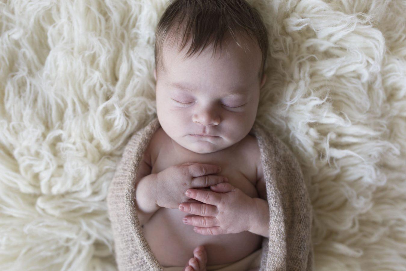 Babyfotografie Hamburg - das kleine Mädchen schläft ruhig auf einem Flokati