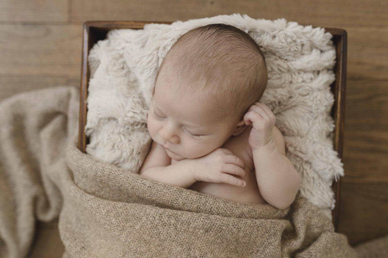 Babyfotos in Hamburg - kleiner Junge schläft auf einer kuscheligen Decke mit einem Bärchen im Arm