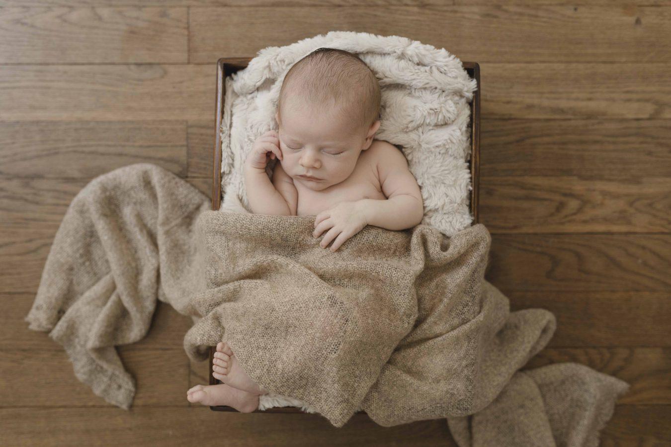 Babyfoto - kleiner Junge schläft auf einer kuscheligen Decke