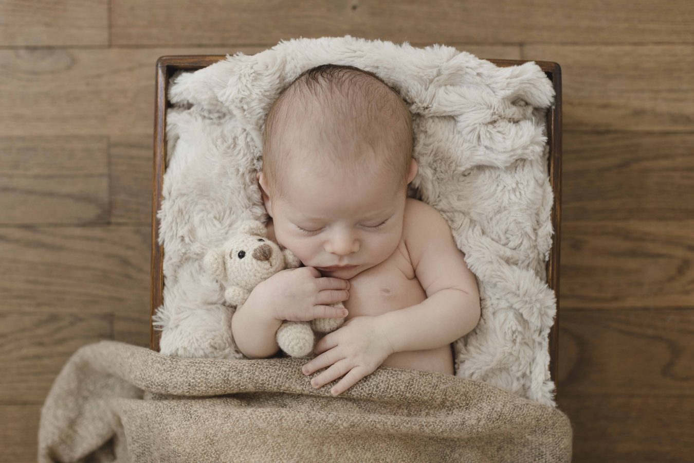 Babyfoto - kleiner Junge schläft auf einer kuscheligen Decke mit einem Bärchen im Arm
