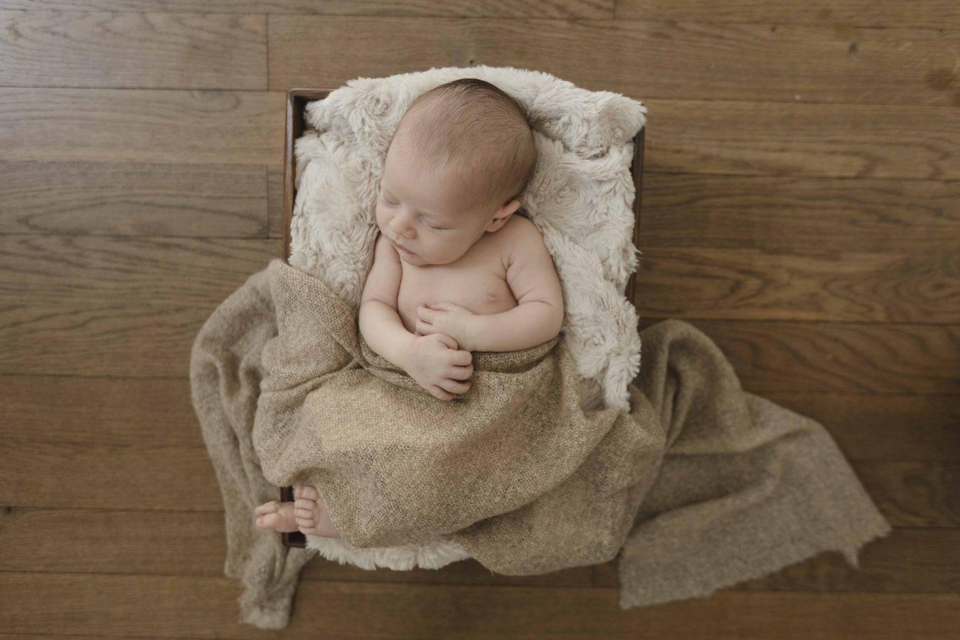 Babyfotografie - kleiner Junge schläft in einer Decke eingekuschelt