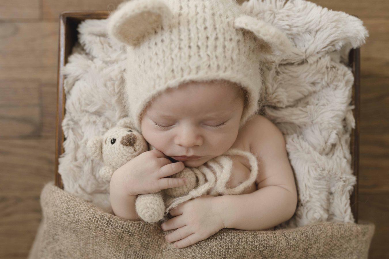 Newbornfotografie Hamburg - kleiner Junge kuschelt mit seinem Teddy