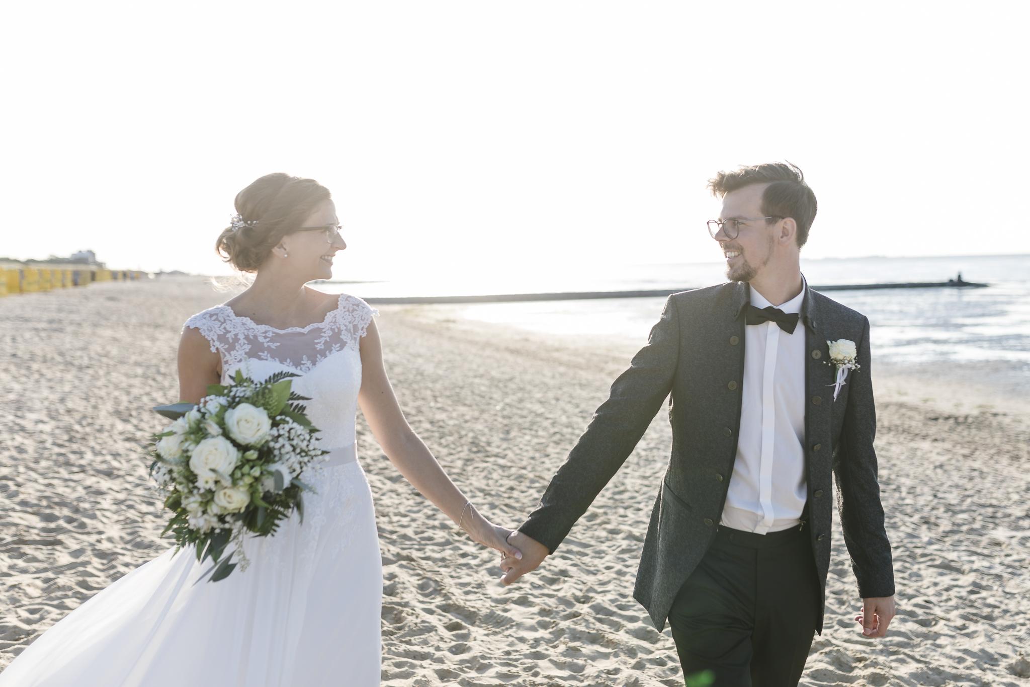 das Brautpaar geht Hand in Hand den Strand entlang