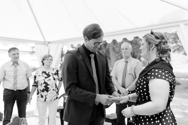 der Bräutigam steckt seiner Braut den Ring an