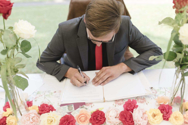 der Bräutigam unterschreibt die Heiratsurkunde