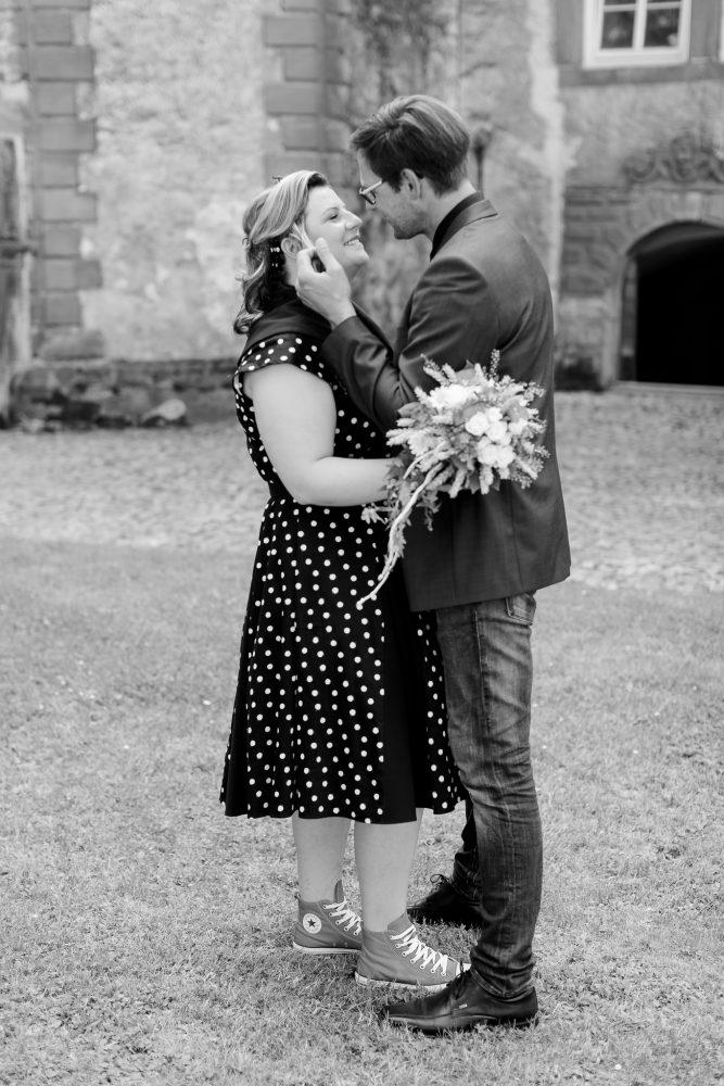 der Bräutigam streicht seiner Frau liebevoll eine Strähne aus dem Gesicht