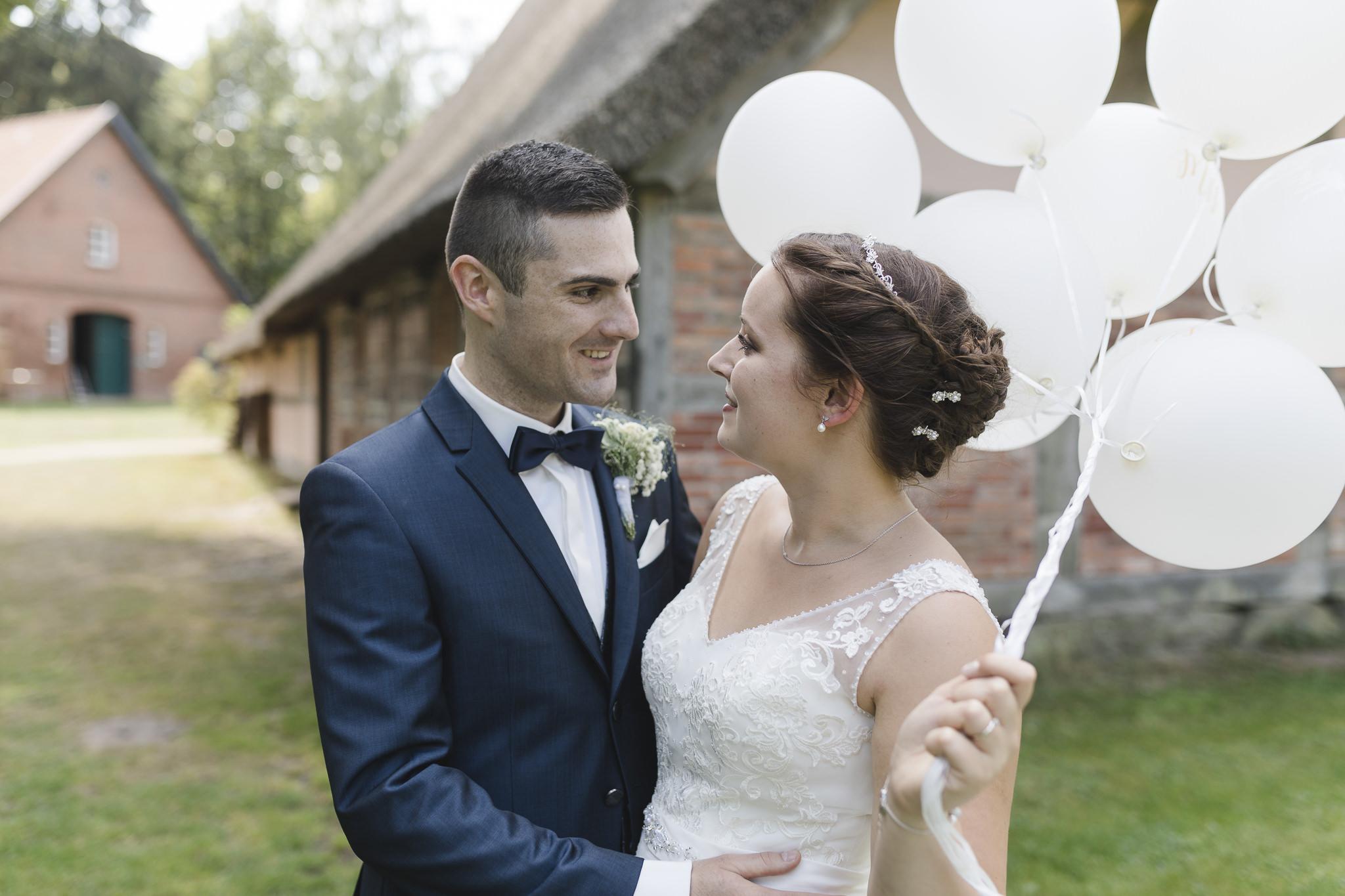 das Brautpaar posiert mit Luftballons bei ihrer Hochzeit im Sniers Hus in Seppensen