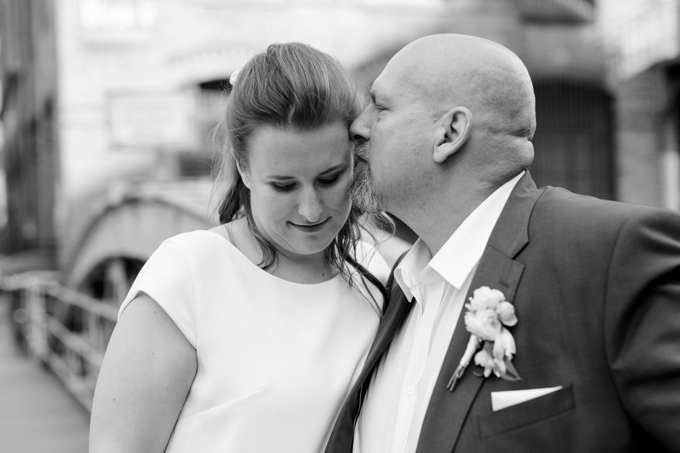 der Bräutigam küsst seine Frau